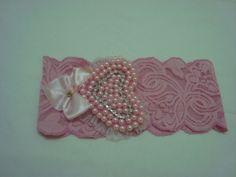 Faixa em renda com elastano com lindo coração em pérolas rosa com strass e lacinho decorativo para deixar sua linda princesa encantada. R$ 19,90