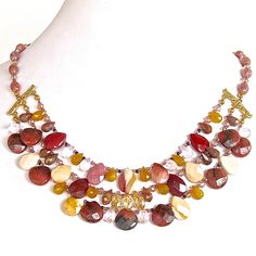 """LANA- Gorgeous gemstone bib necklace Brimming with semi-precious drops in warm holiday hues.Goes great with """"Marsala""""-Pantones color for 2015- Composed of beautiful moukaite in wine, ochre and almond, delicate pink rose quartz, glowing goldenrod opal glass and crystal; this statement piece will make an ordinary outfit – extraordinary. https://earthandmoondesign.com/shop/etherea/lana-18-inch-gemstone-bib-necklace/"""