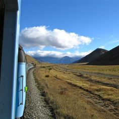 TranzAlpine - The journey starts in Christchurch, and heads out over the sprawling Canterbury Plains. The train stops in a few outlying farming towns, inching ever closer to the Southern Alps that can be seen looming protectively on the horizon.