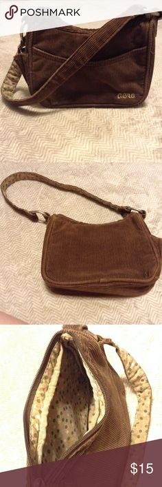 Aero Brown Corduroy Small zippered Purse This sassy small purse has an open pocket on front, and small pocket on the side for essentials (lipgloss or sanitizer). The inside is tan with brown, sage, cream and pink polka dots. There is a zippered pocket inside to hide or hold the essentials. The strap is held on by metal rings and is brown corduroy on top with the inside print on the bottom of the strap. It's large enough to be a small shoulder strap, but also looks perfect just to carry…