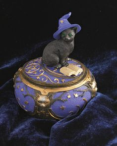 You know cats are magical - but did you know they study at it? Cat in a wizard hat peruses a mystical tome on the lid of this delightful box. $25