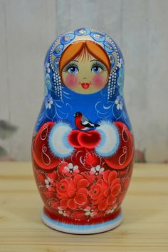 Russian nesting doll in blue and red winter attire with bullfinch in her hands