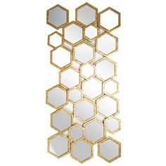 This unusual long wall mirror features a cluster of hexagons of various sizes with gold coloured edging....