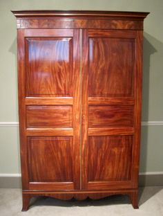 Georgian Mahogany Jersey Wardrobe-A fine late 18th century Georgian figured mahogany Jersey wardrobe, with fielded panel doors, the cornice and shaped apron banded in satinwood, on original splay feet.