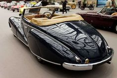 1948 Delahaye 135M Cabriolet Convertible. This old car features an unusual three-position Landau folding top, allowing a middle position (only the rear seats covered), and rear-hinged 'suicide' doors that incorporate the sweeping fender line.