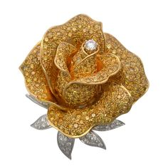 Sabbadini Fancy Yellow Diamond Rose BroochThe elegant rose bloom set throughout with fancy intense yellow diamonds (app. 9 carats total weight) mounted in yellow gold, further enhanced with a single white diamond center and diamond leaves (app. 1 1/2 carats total weight) mounted in white gold, single hinged pin back and safety catch, signed Sabbadini Milano, Italian, ca. 1985.,