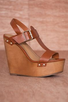 Renew your wardrobe in these tan faux leather platform wedge sandals With a strappy design including a t-strap vamp and a buckled ankle strap these open toe sandals can be worn all season long