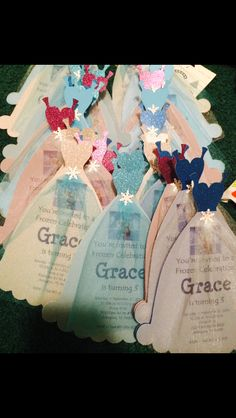 """Frozen Invitations - made with cricut cartridge """"birthday cakes"""".  Used glitter card stock with a vellum over the bottom of dress layered again with tulle over the bottom portion of dress then pinned together with a snowflake brad.  (All purchased at hobby lobby)"""