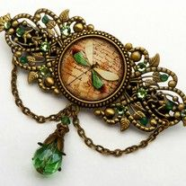 This enchanting dragonfly hair clip is made in antique style and a lovely summer accessory. It consists of a hair clip base, made of bronze coloured metal, with hair clip mechanics on the back (width 6.5 cm). On the front is a round jewelry setting with handmade glass cabochon which shows a beaut...