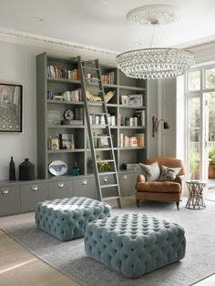 Love the contrast between the fixture and mouldings// bookcases, tufted ottoman, leather armchair, modern chandelier