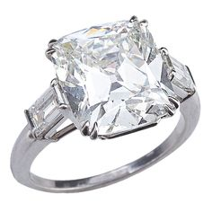 Brilliant Cushion Cut Diamond Ring  circa 1940  The platinum ring centers a 6.53 carat cushion brilliant-cut diamond, color: J, clarity: SI1 (with GIA certificate) flanked on either side by 1 baguette-cut diamond.  Price  $125,000