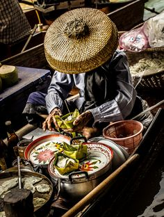 A stunning figure sitting in one of the floating markets of Thailand by Giovanni D'Errico