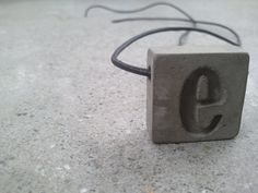 Concrete Jewelry  - Natural gray with etched letter e urban fossils.