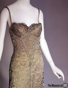 This classic lace slip dress - a nod to lingerie - integrates the sensual, feminine quality of Chantilly lace with the hard look of silver metal. Its look is refined, sexy, and ultimately daring. Calvin Klein's designs have chronicled the progress of the women's movement, and this dress, like much of his work, acknowledges a woman's prerogative to decide how and when to wear her clothes. eMuseum - View Media
