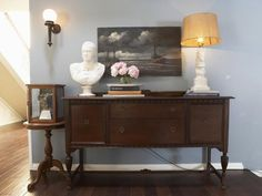 The wall opposite the windows is painted a soft blue, and a vintage buffet is brought in to serve as a credenza and provide storage in the living room. Accessories like an oil painting, sculptural horse lamp and a concrete bust add traditional style to the space.