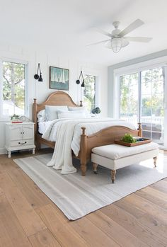White and Blue lake house master bedroom. Rustic warm woods, white planked walls, and pale blue/gray walls give a serene feeling to this lake home.