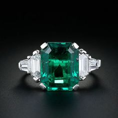 A simply stunning and substantial emerald is the star of this classic platinum ring. The 5.11 carat vibrant bluish green emerald is embraced on either side by a high quality hexagonal and tapered baguette cut diamond giving the ring a clean architectural design.