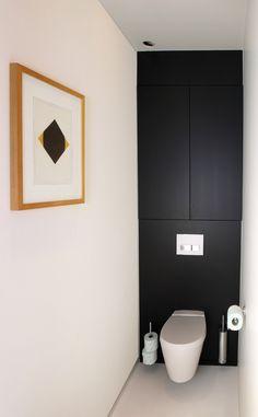 Les toilettes arborent une déco simpliste en jouant sur un côté minimaliste très tendance. Une touche moderne qui se poursuit dans l'intégration des rangements. En effet, encastrés dans le mur peint d'une couleur noire mate, ils disparaissent complètement et n'encombrent pas la pièce. Un moyen de dissimuler astucieusement tous les objets disgracieux présent dans les toilettes. Et pour donner du style au serviteur et à la brosse, on leur fait prendre de la hauteur.