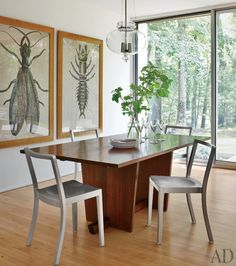 Philippe Starck chairs by Emeco surround a vintage Nakashima table in the dining area of a renovated 1964 modernist home in Connecticut — archdigest.com