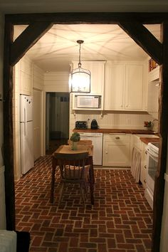 galley kitchen with white cabinets, carriage light, wood counters, wood beams and brick floors