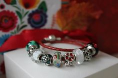 PANDORA Bracelet on Braided Leather with Pretty Murano and Enamel Charms.
