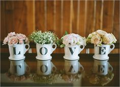 """Use lettered mugs to spell the word """"love"""" and fill with flowers for an easy and inexpensive addition to your decor."""
