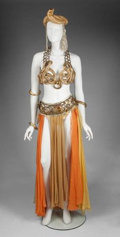 MARILYN MONROE THEDA BARA CLEOPATRA COSTUME comprised of a goldtone brassiere with snake motif cups, prong set costume gems and metal ring straps, and a skirt created by a series of of scarves affixed to a gold lame bikini bottom. The accessories include a serpentine headdress with goldtone linked rings at each side, three pressed metal wristbands and armbands with arabesque designs, and a belt designed to be worn at the hip with goldtone bead, gen and paillette embellishments.
