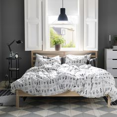 A rustic bedroom with a FJELLSE bed in untreated wood, SÖTVÄPPLING graphic quilt cover in white and black and GUNNERN pedestal table.