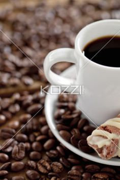coffee beans and drink with cookie - Close-up of coffee drink and cookie with beans in abundance