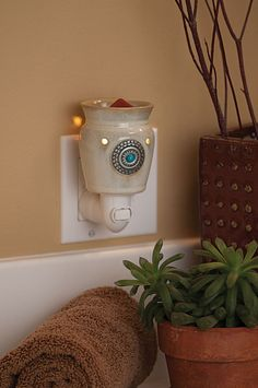 Santa Fe Plug-In Scentsy Warmer    Conjure up images of New Mexico with this weathered taupe warmer accented by a pressed silver-and-turquoise medallion.    Your Price: $20.00