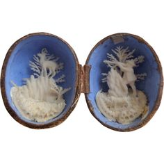 "This plaster painted walnut shell novelty item is most interesting. Once the shell is opened it reveals an interior scene created from salt this is set against a striking blue background for maximum effect. As images show some of the ferns have been lost due to age but it is still a wonderful item for a large dolls house display or similar. The background is painted a deep blue and really shows off the figural detail. It measures just 2.25"" wide"