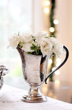 ...roses in an old silver pitcher...clever use of beautiful antiques...