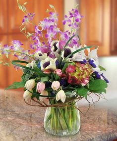 Joyful Dreams. An inspirational display of spring beauty. Two toned calla lilies, tulips, hydrangea and orchids designed together in a compact design with accents of greenery, bear grass and curly willow wrapped around the neck of the vase to create a memorable sentiment.