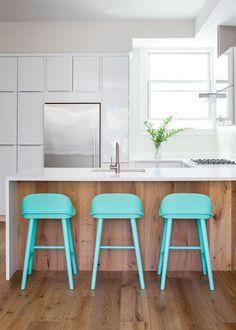 As banquetas em verde água deram o toque de cor e descontração que faltava nesta cozinha minimalista! O projeto é da designer de interiores Nicole Newkirk. Foto: Helyyn Ospina