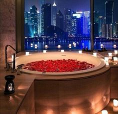 Bathtub full of rose peddles and candles with wine and a book