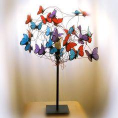 Lámpara hecha de alambre rojo, púrpura y azul de aluminio con mariposas rojas, púrpuras y azules de papel translúcido vegetal. Es un objeto bello cuando está encendido o apagado.  Cuando está encendida, las sombras de las mariposas proyectadas en el techo o las paredes le dan al ambiente un aspecto teatral.