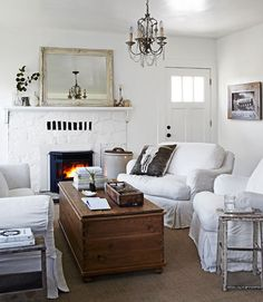 Love the chandelier and the white furniture..