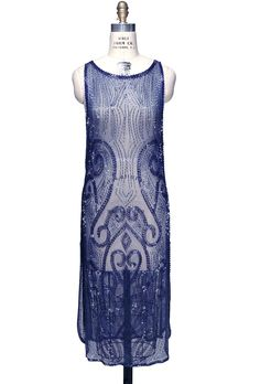 Our Vignette overlay gown is a true piece of Deco art! Handbeaded on sheer mesh, it has a fabulous curvilinear design all over. Chic low armholes and side slits complete the sexy look. Sheer, so a sli