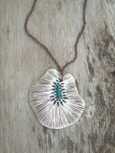 I created this sculptural pendant out of porcelain. The design is based on a microscopic seed. The piece was rubbed with a deep sepia glaze, which was wiped away to reveal the details before adding the bright turquoise glaze.  It has an antique copper toned chain measuring 17 long. Please let me know if you would like a different chain length.  The pendant itself measures about 2 X 2.