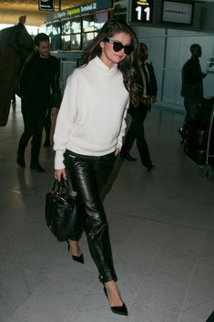 Selena Gomez spends a lot of hours on airplanes — just in the past few weeks she has visited New York, Miami, London, and Paris to promote her new album, Revival, out Oct. 9, and her movie Hotel Transylvania 2. And through the years, the singer and actress has picked up a trick or two about dressing warm for the frigid temperatures inside the plane, always being ready for the paparazzi, and packing a practical but gorgeous bag with all the essentials.