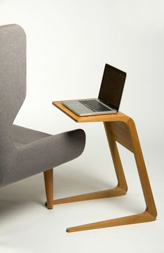 Riley is a solid wood, pull-up table designed by Sam McMorran that lets you do work on your laptop or hold a drink within arm's reach.