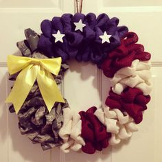 Patriotic american flag wreath made from colored burlap, military uniforms (ABUs or ACUs), white stars, & yellow bow.