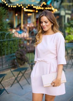 Girly look with pink mini dress, pearls, and YSL clutch.