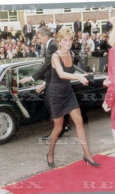 Diana Princess Of Wales - 1995 She Chose A Short Black Dress. He Followed The Regulations In A Long Black Tailcoat. Diana Attending A Charity Premiere Of The Tom Hanks Movie 'Apollo 13' Was The Model Of The Modern Woman Stealing The Show In Her Stunning Versace dress.