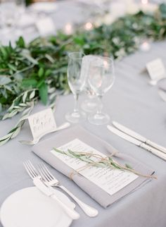 I love all of the details on this table: the garland, the napkin and menu tied together with twine, the simple dishware and flatware, the tablecloth. Photography: Diana McGregor - www.dianamcgregor.com Read More: http://www.stylemepretty.com/2015/02/12/romantic-ivory-grey-ojai-valley-inn-wedding/
