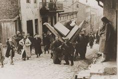 Ebrei espulsi dalle loro comunità trasportano i residui averi sotto gli occhi dei civili, 1942