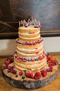Yummy naked wedding cake with summer berries made by Little Lucy's Bakery in Braintree. Cake on a wooden stand making it more rustic and a calligraphy Mr & Mrs wedding cake topper. #weddingcake #nakedcake #essexwedding