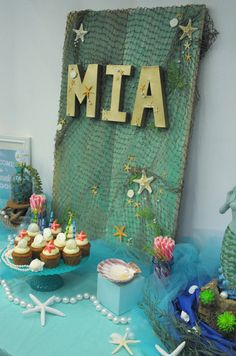 """o create Mia's name and make a """"splash"""" (I do love a good pun!), I picked up papier mâché letters and spray painted them a metallic gold first, followed by a glitter gold. Gold is so easy to do and really glams things up quickly. Evite-Party-Ideas-Fern-and-Maple-Contributor-Mermaid-Party-backdrop"""