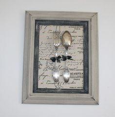 Sur un support en tissu imprimé en lin des couverts en métal argenté joliment ciselés on investis ce cadre en bois patiné deux tons , le tour extérieur en couleur lin chaul - 18973544