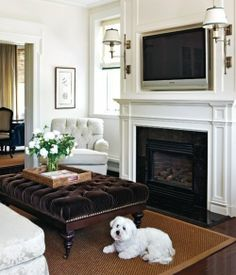 living room, white walls, brown velvet tuffetted ottoman, neutral rug, fireplace (puppy!)